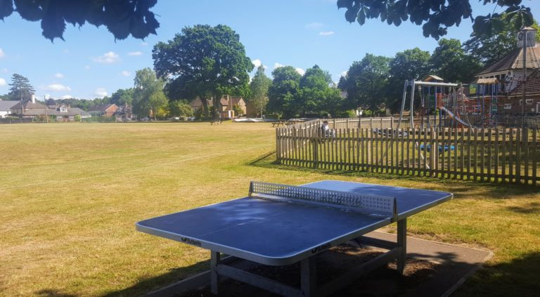A view of the Thursley Road Recreation ground, with the blue outside table tennis table in the foreground, behind which is the children's play area and the cricket ground.