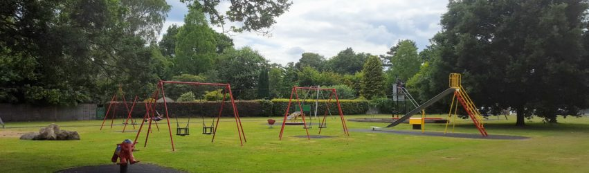 Burford Lodge Recreation ground showing play equipment - swings, roundabout, slide and zip wire.