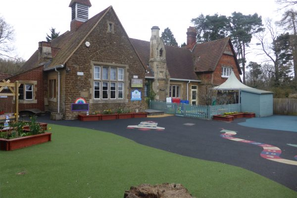 St Mary's School building - a Victorian stone building, with a play area in front. There are planters with daffodils and hopscotch markings on the ground.