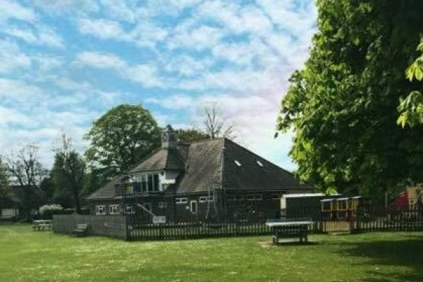 A picture of the Pavilion on the Thursley Road recreation gound, with grass in front and a picket fence surrounding the children's play area.
