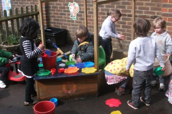 Children having fun with buckets and containers at Rainbows Nursery.